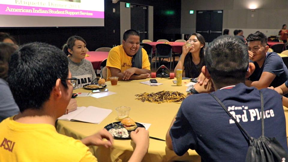 Students sit around a table talking during a SPIRIT event