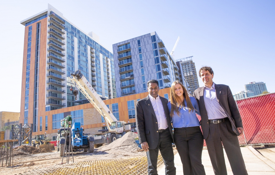 three people standing in front of construction site