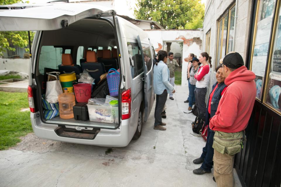 Graduate students from several universities pack a van full of archaeology equipment.