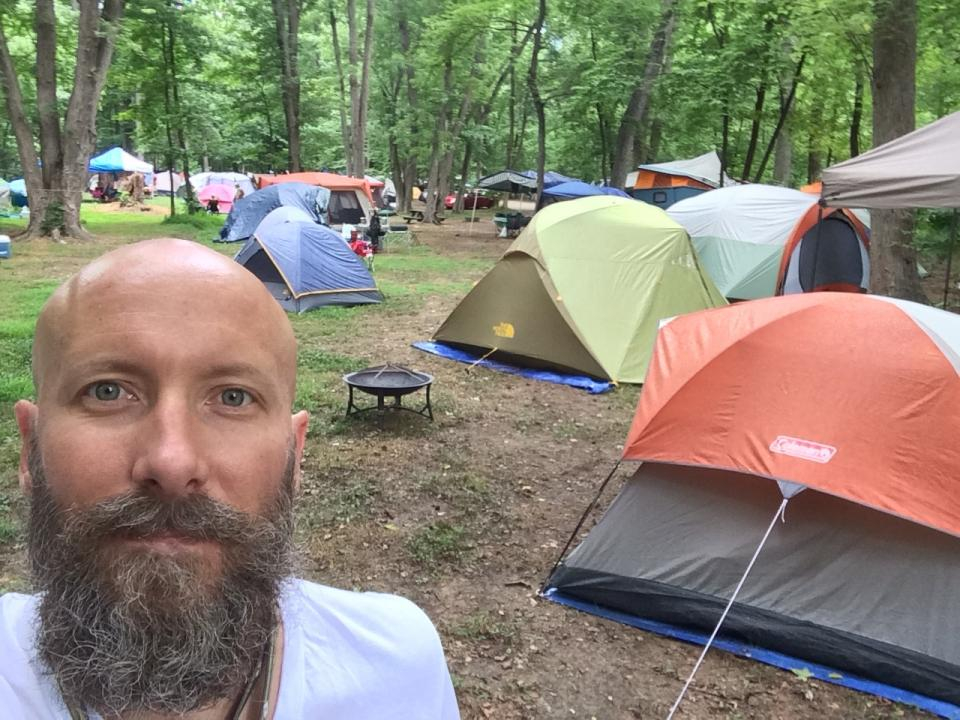 selfie of man in woods with tents
