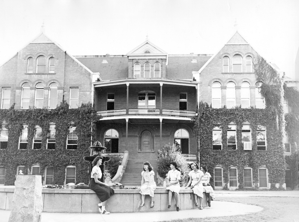 Five women sitting on the fountain in front of Old Main, Arizona State University (ASU), Tempe, Arizona (circa 1940)