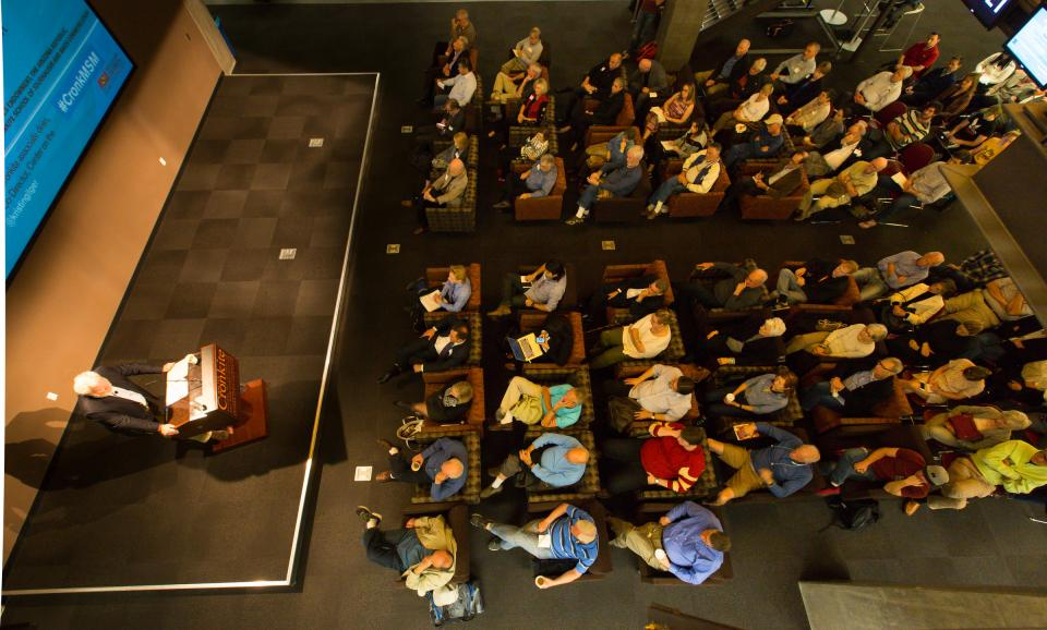 An aerial photo of a crowd listening to a speaker inside the Cronkite School.