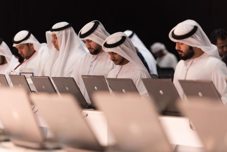 UAE men stand at a line of laptops