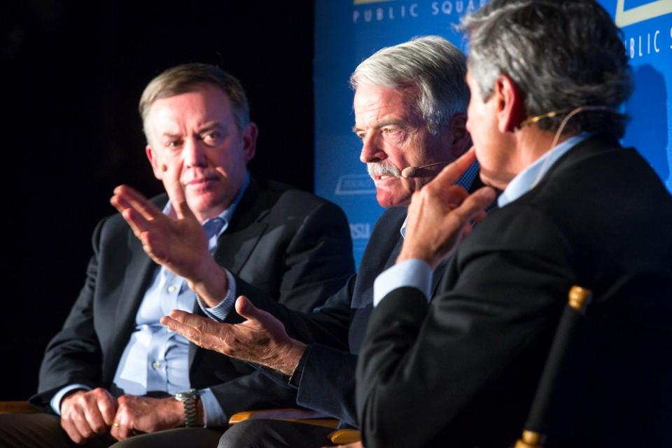 Three men discuss universal health care on a stage.