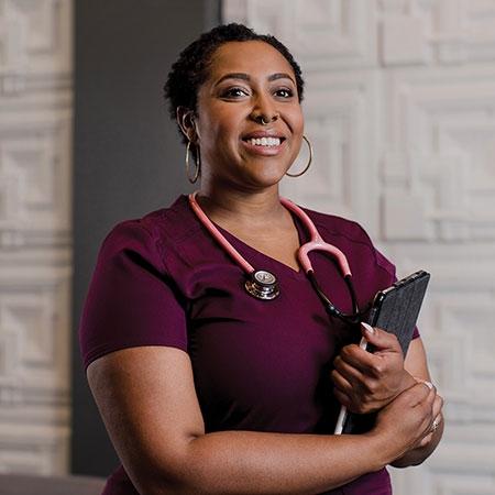 Portrait of ASU Online grad Desiree Brionne Dillard in medical scrubs