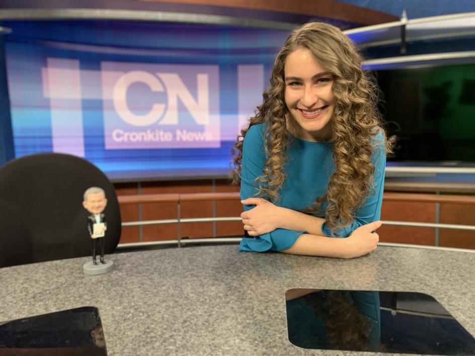 ASU Cronkite student sitting at news desk