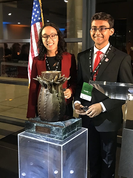 Two college students stand behind a trophy after winning the 2019 inaugural Regents Cup debate tournament