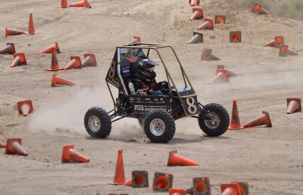 student driving baja car through course