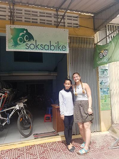 Woman and girl standing in front of a bike shop