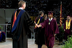 graduate walking across stage, shaking hand with dean