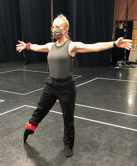 A woman dances in a studio wearing a mask