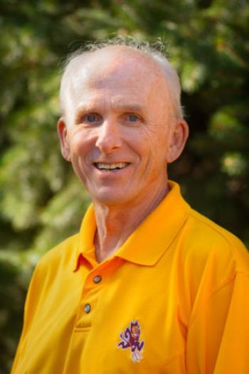 headshot of a smiling man wearing a gold polo with a Sparky the Sun Devil logo