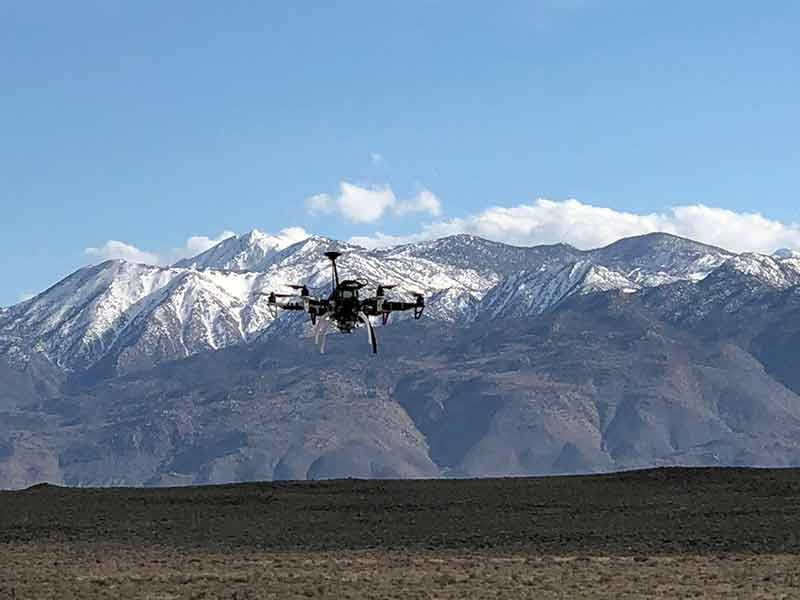 drone flying in front of desert mountains