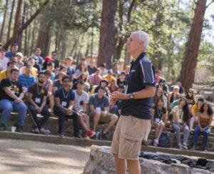 man speaking to students at camp