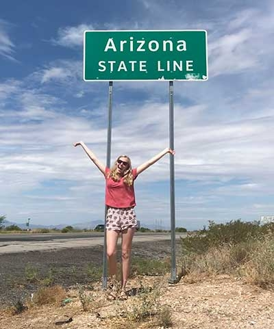 ASU honors student Emily Hagood strikes a happy pose next to an Arizona state line sign on the highway