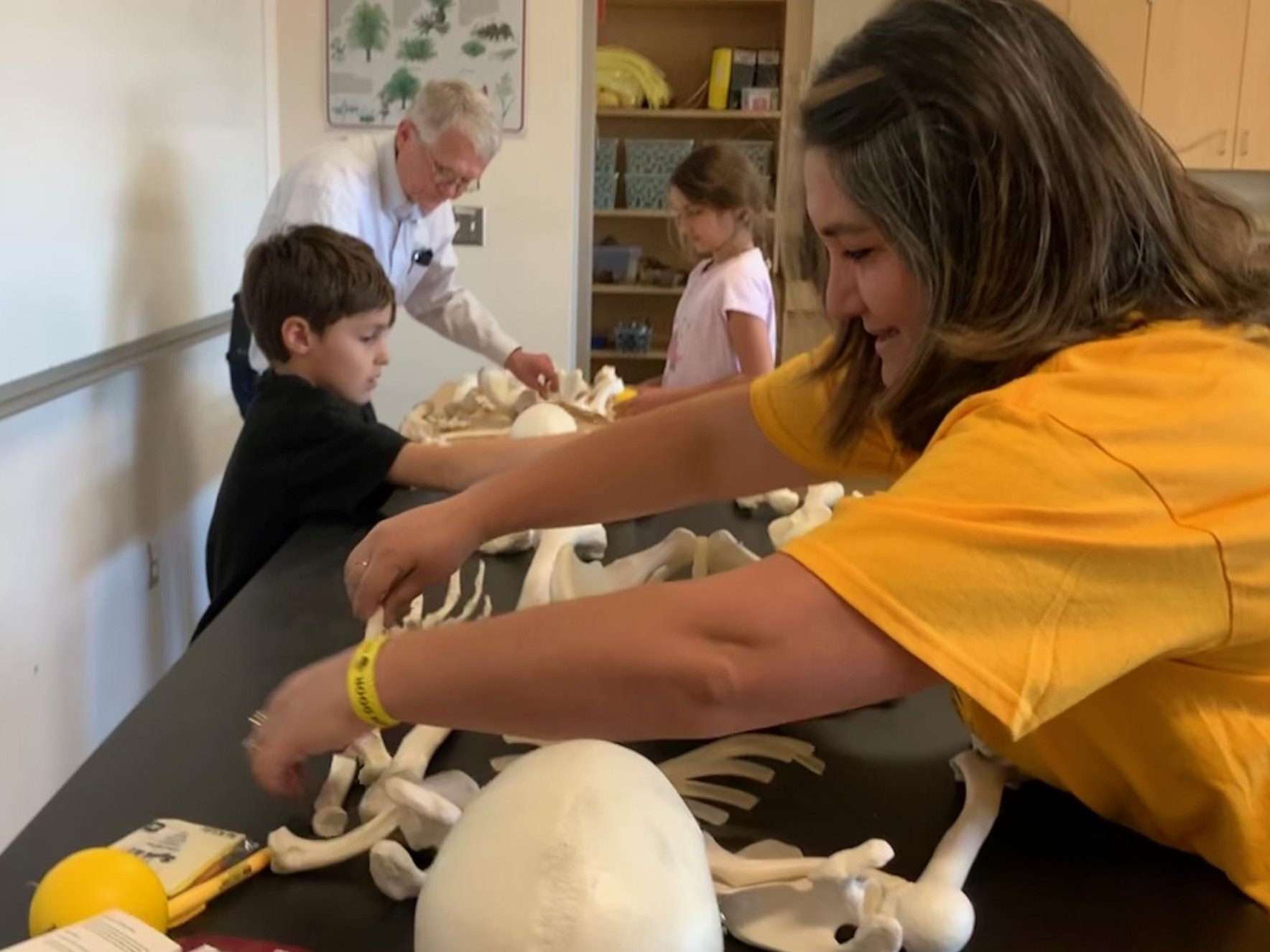 Emel Topal, her son and daughter race with College of Integrative Sciences and Arts dean Duane Roen to assemble lab skeletons at 2019 ASU Open Door event