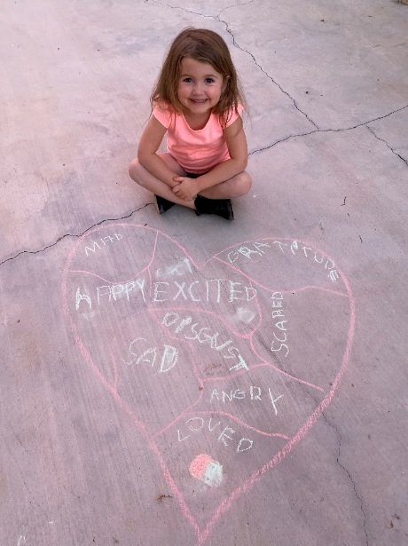 young girl sitting on sidewalk next to heart drawn with chalk