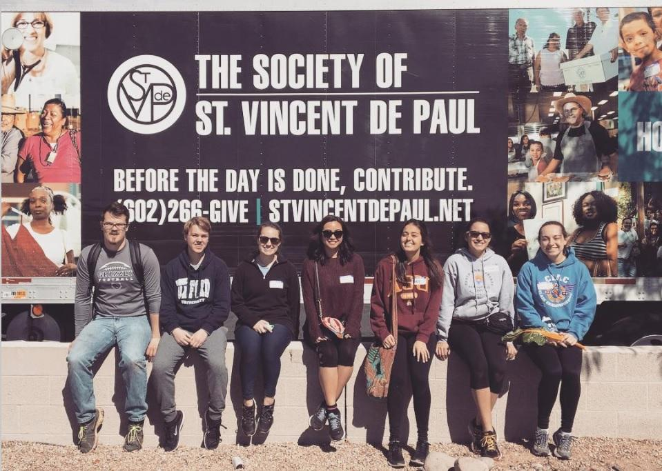 students pose in front of St. Vincent de Paul banner