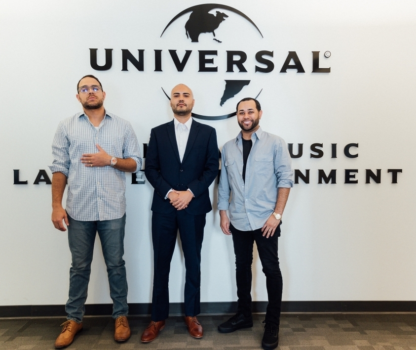 three men standing in front of Universal Music logo
