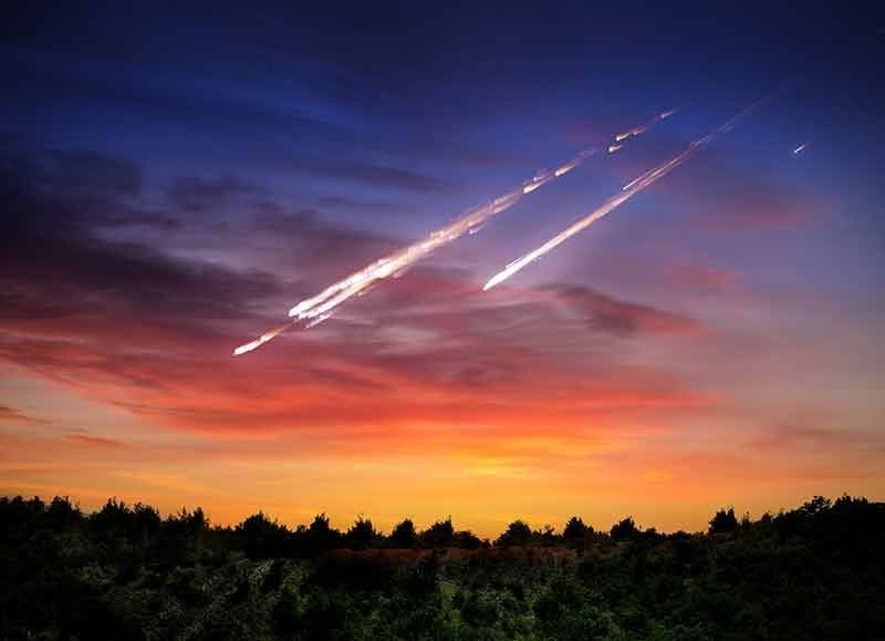 meteorite falling to Earth over treeline