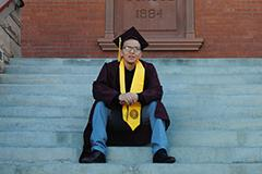 man in graduation cap and gown sitting on steps in front of Old Main