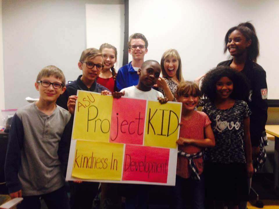Picture of Tracy Spinrad and children holding a sign from Project Kid.