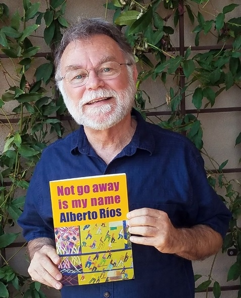 man with white beard and glasses holding a book