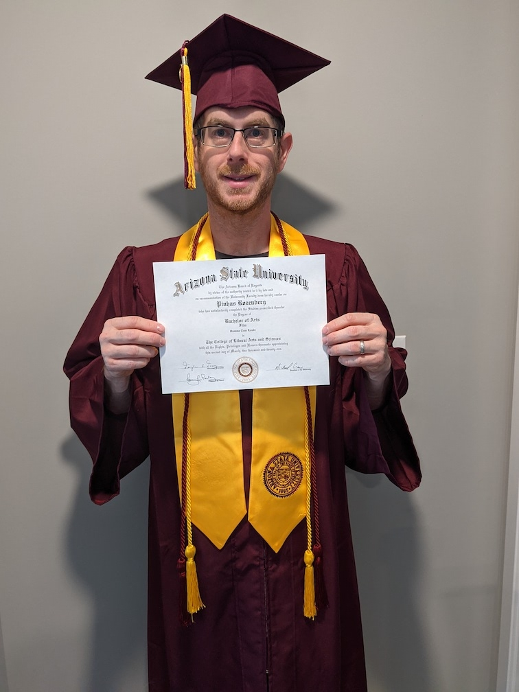 Peter Rozenberg holds his diploma in his ASU regalia