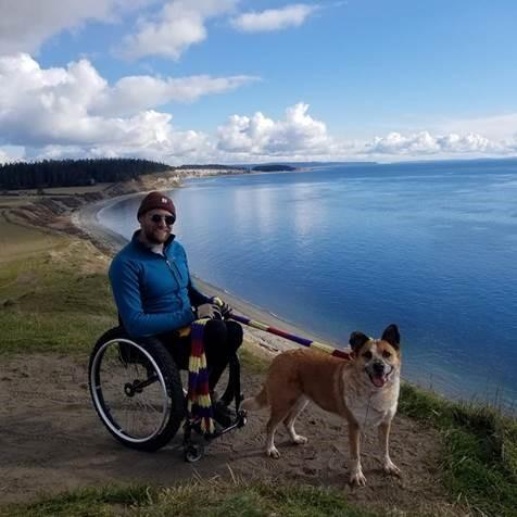 man in a wheelchair with a dog by a lake
