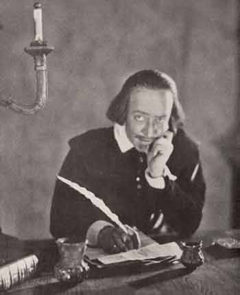 photo of actor as Shakespeare sitting at desk with a mischievous expression