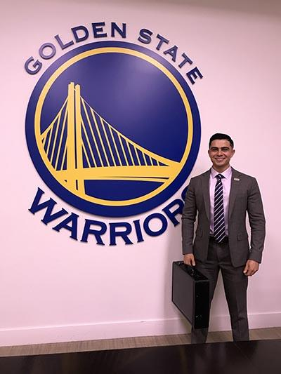 student standing in front of Golden State Warriors sign