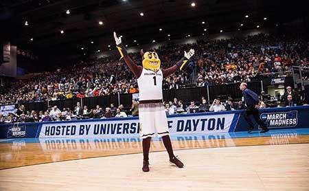 ASU mascot Sparky stands on a basketball court and waves to the crowd
