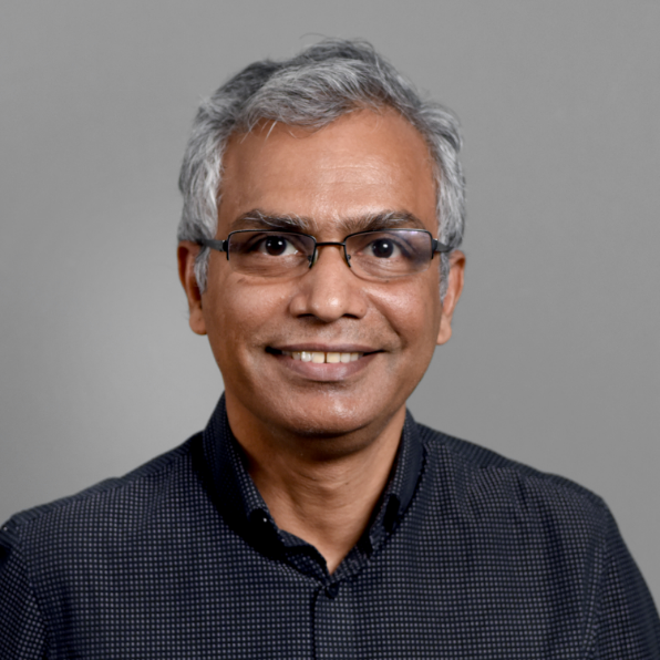 Man with grey hair and glasses