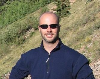 headshot of a man wearing sunglasses and a dark blue shirt with nature in the background