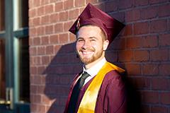 man posing in graduation cap and gown