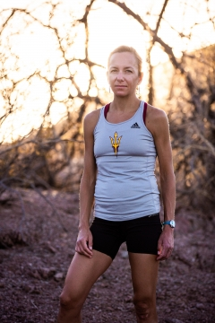 ASU Clinical Assistant Professor and sports historian wearing ASU logo running top and shorts looks at the camera against a backdrop of a desert scene
