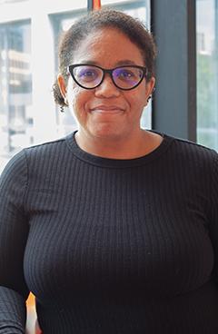portrait of new ASU faculty member Brandi Adams, wearing glasses, a black shirt and smiling