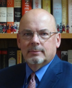 Man in glasses in front of books