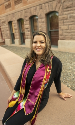 sits near Old Main wearing her graduation stoles and cords