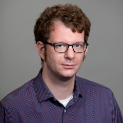 Man in glasses and purple shirt