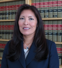 Native American woman with law books in the background