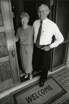 black and white photo of man and women at front door