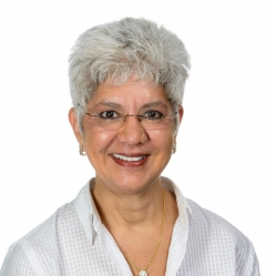 Woman in grey hair and glasses smiling