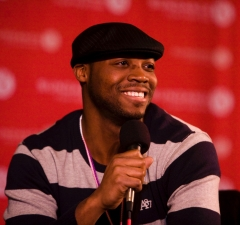 speaks into a microphone while smiling on a film festival stage