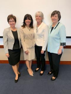 four women standing in hallway