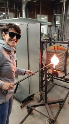 woman putting rod into glass blowing oven