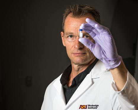 ASU researcher holding up vial