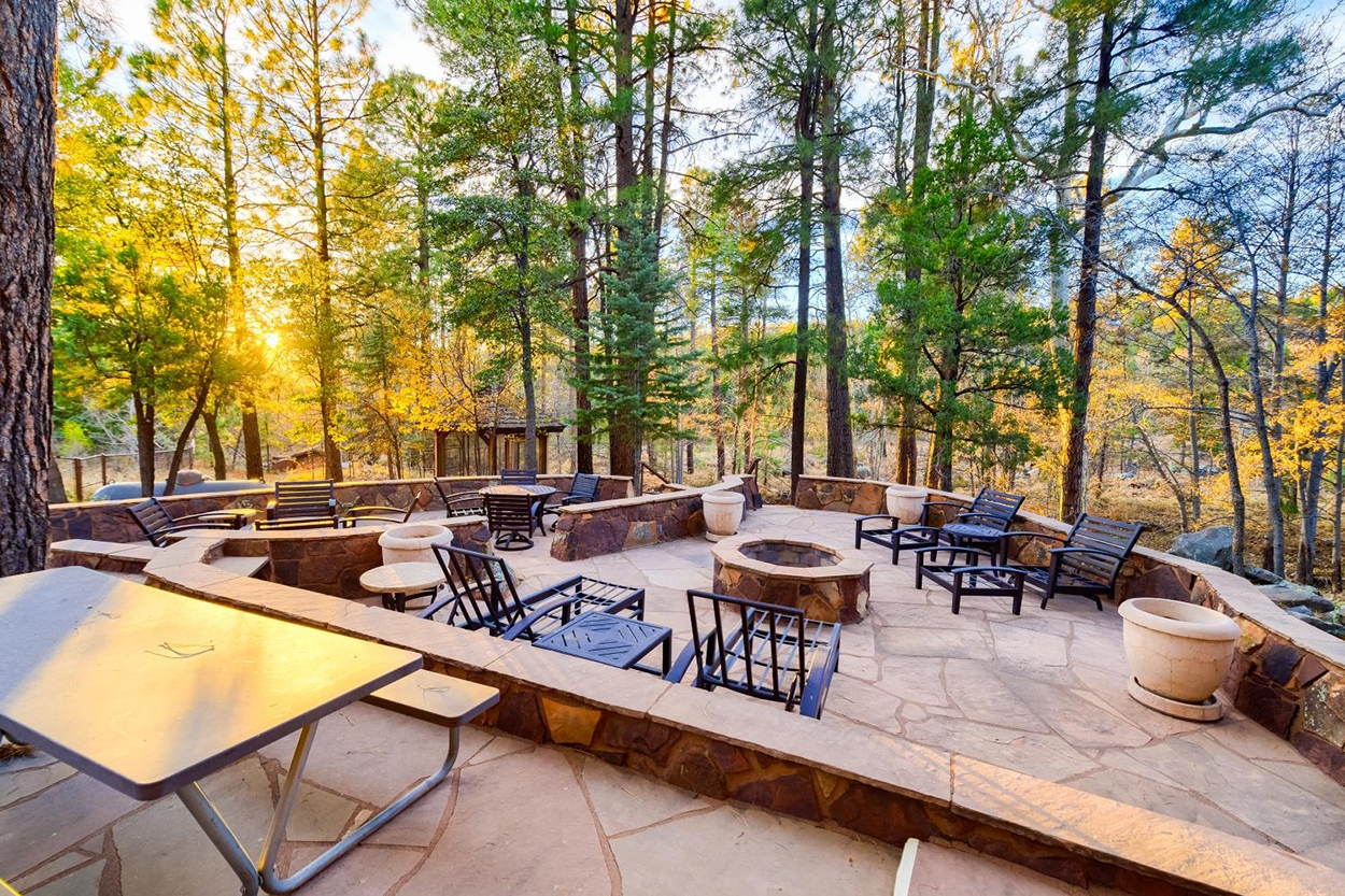 A large stone patio with several seating areas and a firepit overlooks Ponderosa pine trees.