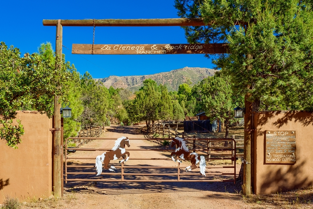 Wood and metal gate entrance that displays La Cienega and Rockridge ranches with trees and mountains surrounding them