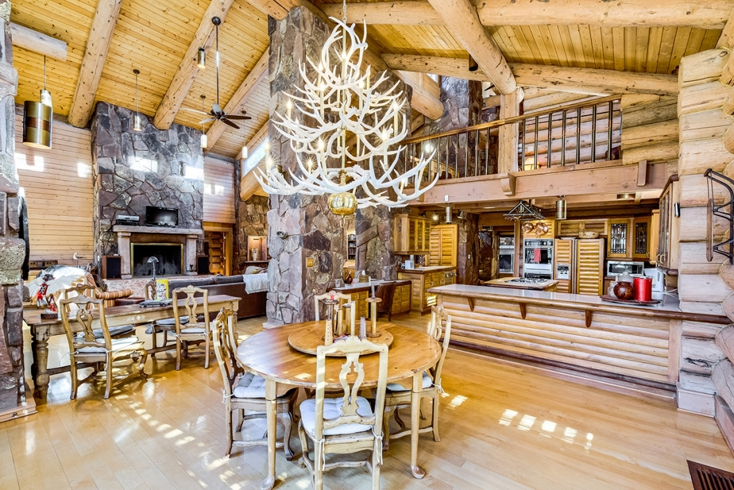A log home displays vaulted exposed beams, a stone fireplace, open log kitchen and  seating area with antler chandelier